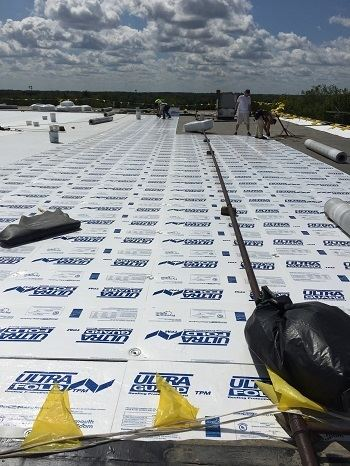 Watertown Industrial roofing contractors installing a new flat roof on a manufacturing plant