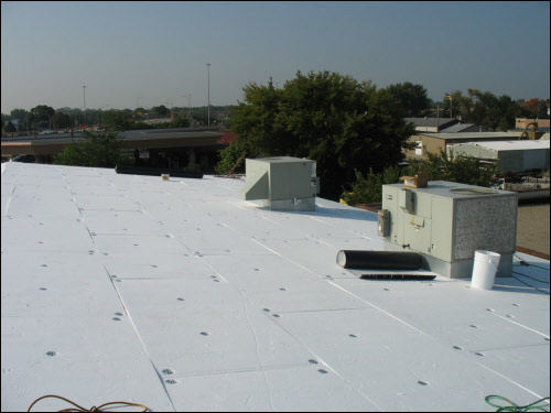 Installing a new TPO membrane over a metal flat roof (mid-process) on an industrial building in Wisconsin